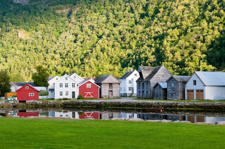 Old wooden houses near pond at the foot of the mountain in Laerdal, Norway photo