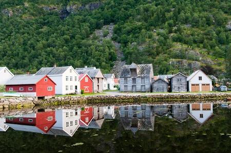 Vecchie case di legno vicino laghetto ai piedi della montagna in Laerdal, Norvegia Archivio Fotografico - 10906192
