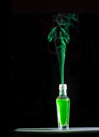 genie woman: Absinthe Green Fairy. Smoke from the bottle. Isolated on black. Stock Photo