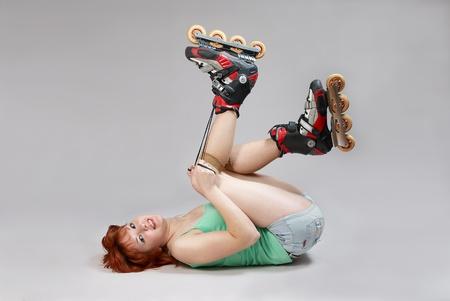 Giovane donna su pattini a rotelle sdraiato sul pavimento e allacciatura. Studio girato su sfondo bianco. Archivio Fotografico - 10943225