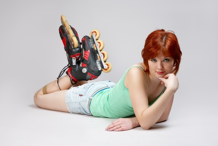 inline skating: Smiling beautiful young woman on roller-skates lying on the floor , on white background. Studio shot