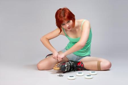 Giovane donna seduta sul pavimento e riparazione pattini a rotelle. Studio girato su sfondo bianco.