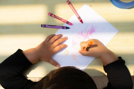 little girl drawing with crayons on paper.topview