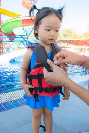 A father helping his daughter with her life jacket.