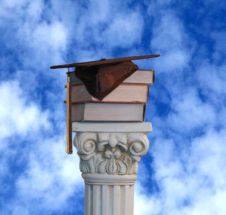 Graduation hat and books on pedestal