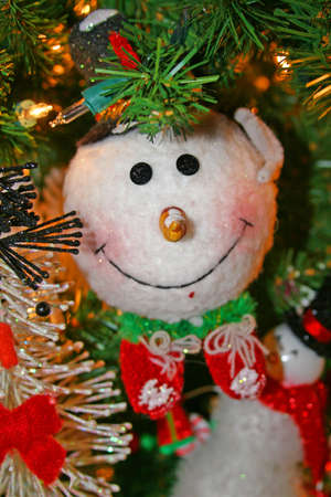 Happy snowman decoration on beautiful green Christmas tree with Christmas lights