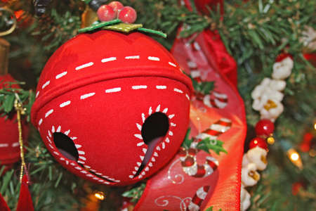 Large red jingle bell on Christmas tree against green branches.