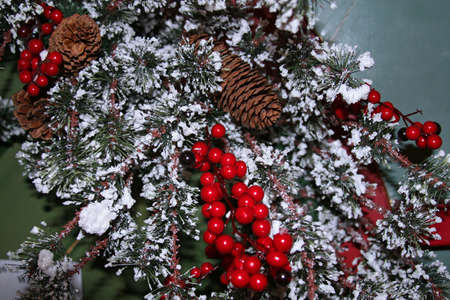 Christmas wreath with snow, red berries and pine cones