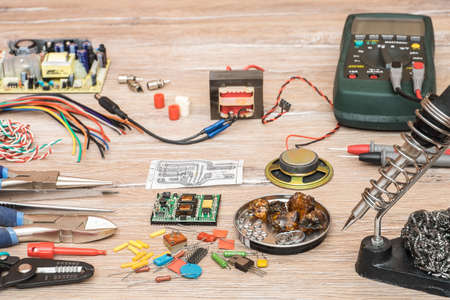 electrolytic: Tools for the designing and repair of electronic devices. Soldering iron, tools, electronic components, wire, devices and multimeter on a wooden table.