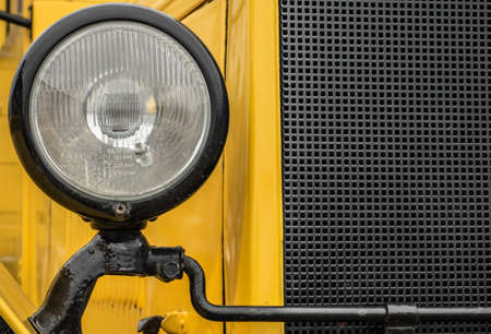Closeup of headlight on vintage yellow truck. Fragment of the old Russian ZIS-5 truck.