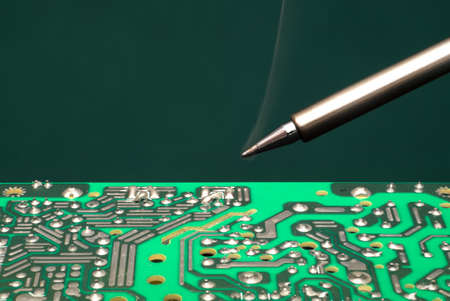 brazing: The warmed soldering iron over the electronic circuit board. Workplace for installation and repair of circuit boards.