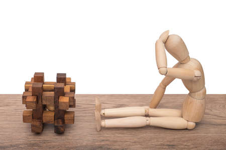 cube puzzle: It is a difficult task. Wooden dummy thinks of the solution of a cube puzzle. Isolated on white background. Stock Photo