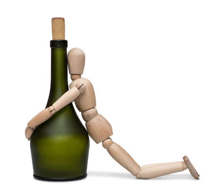 intoxication: Hard drinking. The lay figure sits near a bottle with alcohol. Isolated on the white background. With shadow.