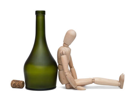 Hard drinking. The lay figure sits near a bottle with alcohol. Isolated on the white background. With shadow.