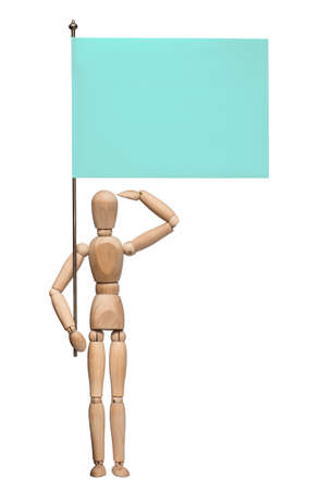 wooden figure: The wooden lay figure with a flag stands at attention and salutes. Isolated on the white background. With shadow.