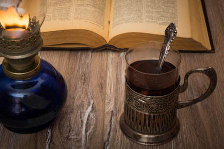 tea lamp: Tea drinking by the light of an old oil lamp. Glass oil lamp, glass with tea in the cup holder and open book on the wooden table. Stock Photo