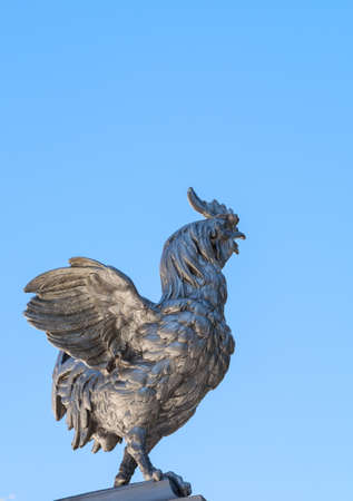 metal sculpture: Metal sculpture of rooster on a blue sky background.