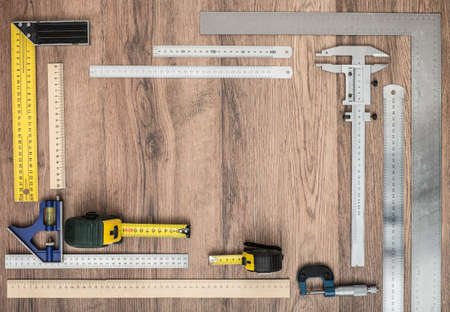 micrometers: Measuring tools on wooden background. Wooden and metal rulers, tape measures, tape-lines, micrometers, set squares.
