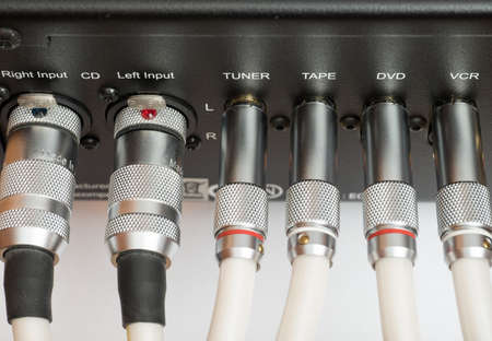 outputs: Sockets and plugs of the inputs and outputs on an black metal panel. It is part of the rear panel of the amplifier. Stock Photo