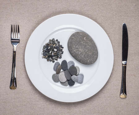 dearth: Guaranteed way to lose weight. Fork, knife and a plate with stones instead of food. Stock Photo