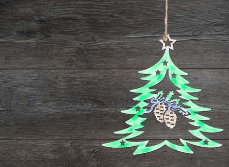 christmas motif: Homemade tree decoration. Christmas motif on background of dark brown wooden planks.