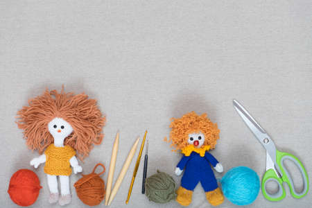 Tools for making knitted toys on gray fabric.