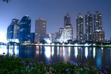 garden city: Vista de la ciudad jard�n con los rascacielos y la reflexi�n en el r�o de la ciudad moderna en la noche en Tailandia.