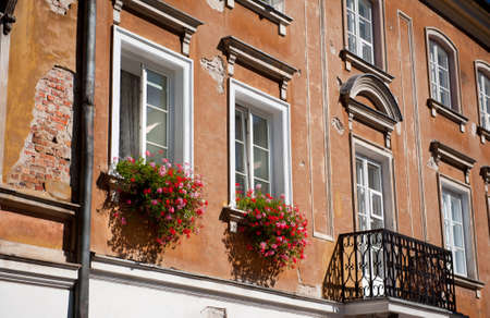 Bunches of pink and red Ivy leaved geranium or Pelargonium peltatum flowers on windowsills and brown damaged wall in Warsaw Old Town, late summertime in Poland. Beautiful ornamental plants outdoors and architecture detail. Horizontal orientation, nobody