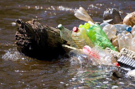 Zoom on plastic garbage damage river after flood in Poland. Scatter empty plastic bottles stuck on log in water, dump environment, objects spilled out, horizontal orientation, nobody. LANG_EVOIMAGES
