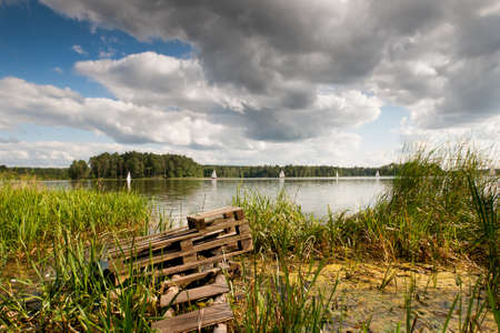 masuria: Old bridge and boats at the lake. Green coastal reeds and sailing boats afar, cloudscape in sunny day. Natural landscape in Ruciane-Nida, Masuria, Poland, Europe. View in horizontal orientation, nobody. LANG_EVOIMAGES