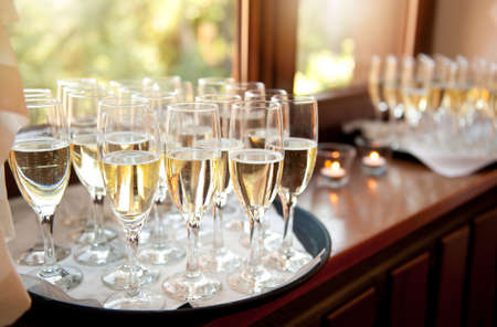 Wedding banquet champagne glasses full of alcohol waiting for bridal guests. Transparent classic glasses with tall stem, objects standing on tray on windowsill, horizontal orientation, nobody