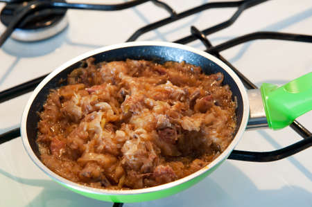 Frying pan with hot Polish bigos, traditional meal known as a hunters stew, popular dish in Poland is served on the Second Day of Christmas. Meal include white cabbage, sauerkraut called kapusta kiszona, cuts of meat and sausages, and occasionally mushroo LANG_EVOIMAGES