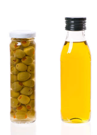 Pickled green olives filled with red pepper and olive oil screwed in glass jars, detail of product isolated on white, studio shot, vertical orientation, nobody.