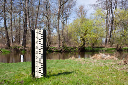 depth gauge: Water flood gauge depth marker and small river called Drzewiczka in Odrzywol, Poland, measuring instrument on shore and trees with fresh green spring leaves afar. Horizontal orientation, nobody.