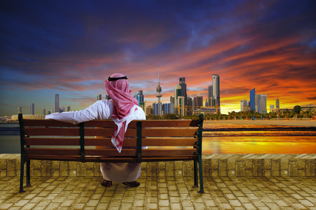 arab men: A man looking at the cityscape of kuwait