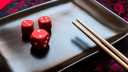 Red wooden dice with a Chinese table background.
