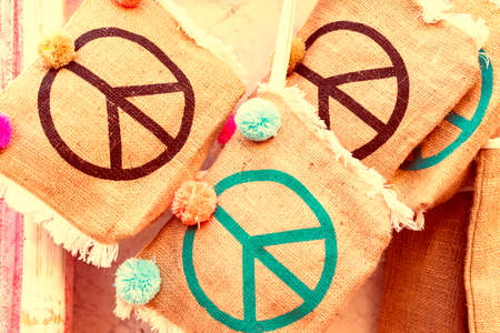 Three bags made of natural materials with the peace symbol of different colors