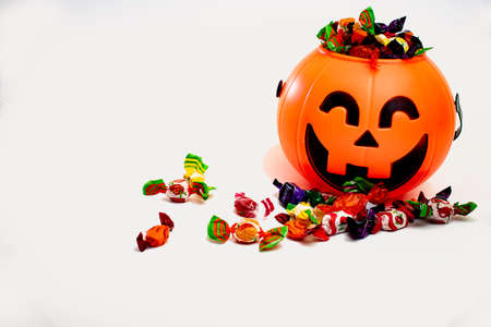 Halloween pumpkin with candies by the side, with white background.