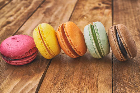 Macarons of different colors with a vintage background on a table of madras