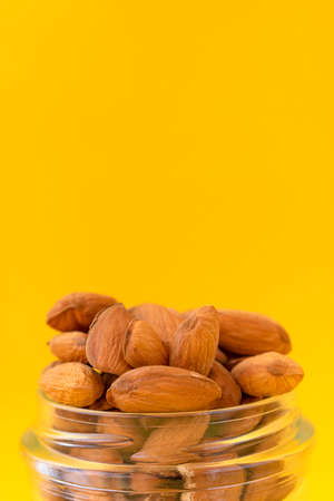 Raw almonds on a yellow background.