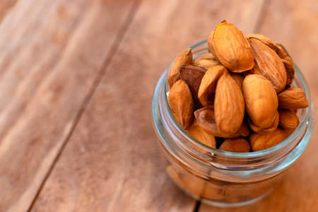 Raw almonds inside a pot, on a wooden table. Stock Photo