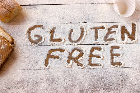 Gluten free concept. Wooden table with flour and pastry material, with the written phrase gluten free.