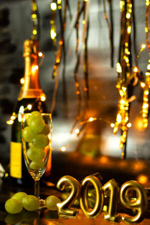 End of the year concept. Glass of champagne with grapes inside, with holiday decoration