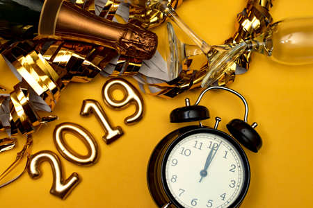 New year concept. Number 2019 with clock and golden party accessories on a yellow background.