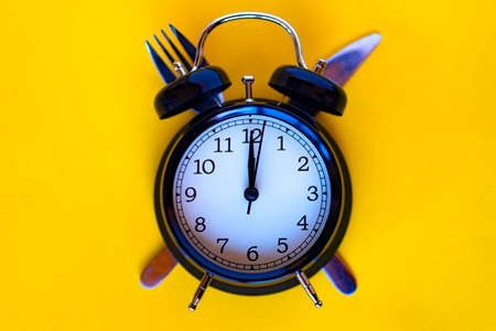 Time concept of dieting. Black alarm clock on a fork and a silver knife with yellow background.