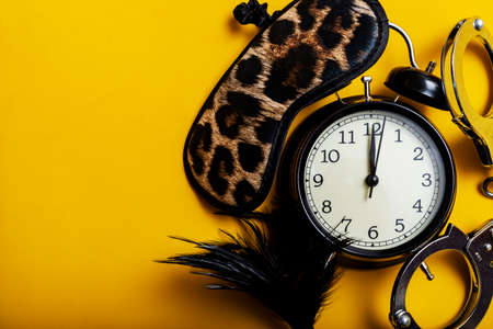 Sex time concept. Black alarm clock with sex toys with yellow background. Stock Photo