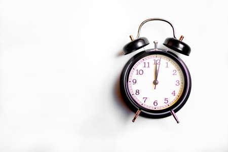 Schwarzer Wecker auf weißem Hintergrund. Konzeptzeit.