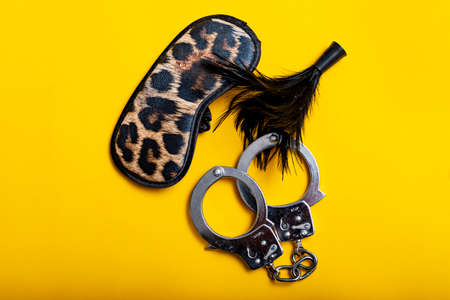 Sex concept. Different erotic toys on yellow background.