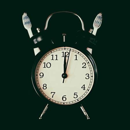 Dental hygiene time concept. Black alarm clock with black background. Banque d'images