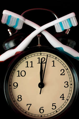 Dental hygiene time concept. Black alarm clock with black background. Archivio Fotografico
